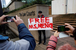A man holds a sign outside of the B.C. Supreme Court bail hearing of Huawei CFO Meng Wanzhou, who is being held on an extradition warrant in Vancouver