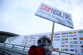 Environmental activist protests against fossil fuel in front of the the venue of the COP24 UN Climate Change Conference 2018 in Katowice