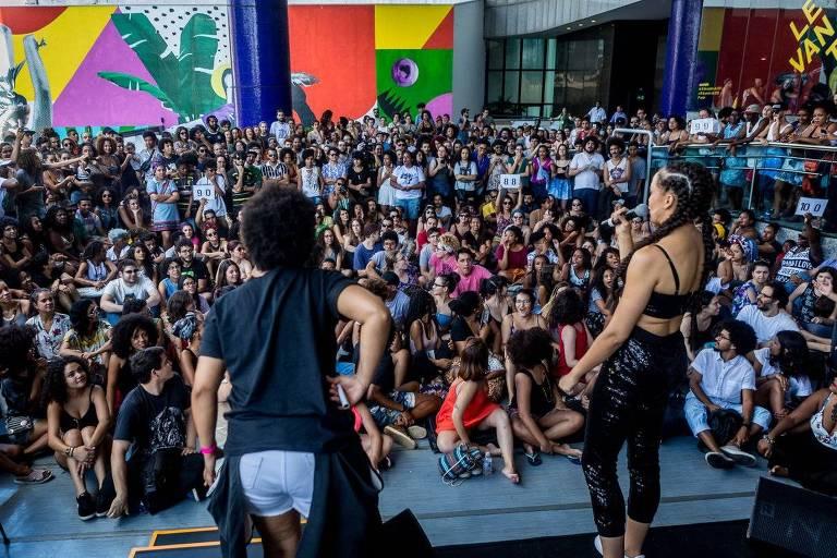 Sentado, o público assiste ao campeonato brasileiro de poesia falada e levanta placas com notas para os participantes. Os poetas declamam textos de até três minutos para tentar bater seu oponente no palco