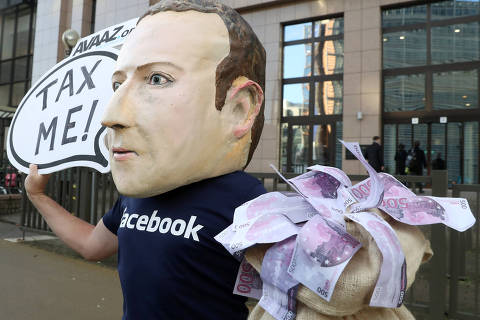 An activist wearing a mask depicting Facebook's CEO Mark Zuckerberg demonstrates during the European Union finance ministers meeting, outside the EU headquarters in Brussels, Belgium, December 4, 2018. REUTERS/Yves Herman ORG XMIT: BRU009