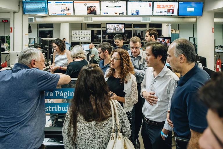A repórter especial Cláudia Collucci guia grupo de leitores em visita à Redação da Folha, em São Paulo