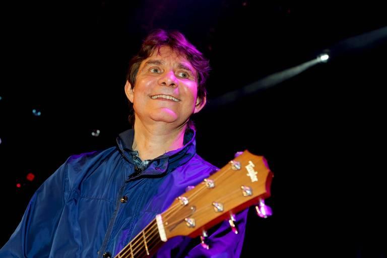 De camisa social azul, cantor Lô Borges segura violão e sorri enquanto é fotografado no palco