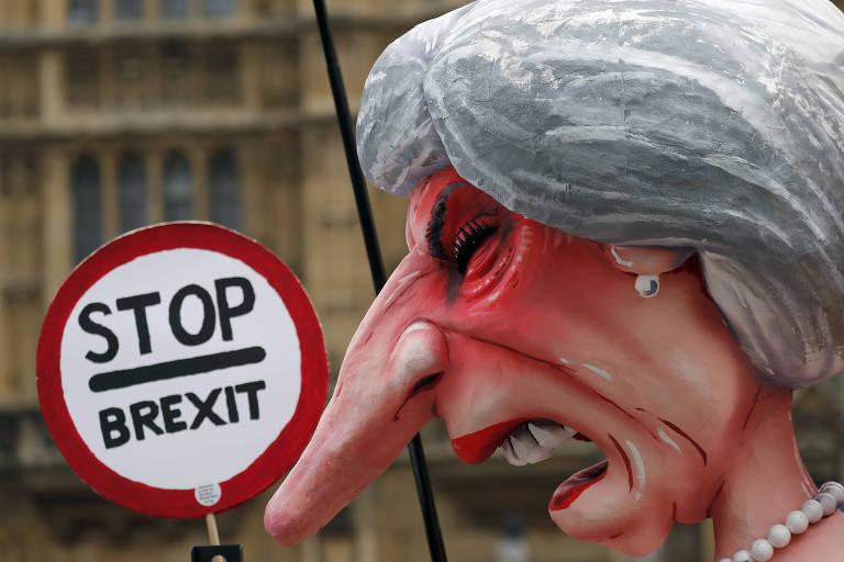 """Close de boneco de Theresa May de expressão irritada e com o nariz alongado, como um Pinóquio, diante de uma placa na qual se lê, em inglês, """"pare o brexit"""""""