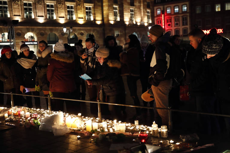 Pessoas se aglomeram diante de velas acesas em uma praça à noite