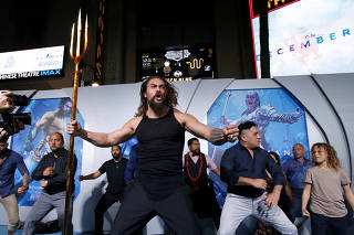 Cast member Momoa performs a haka dance at the premiere for
