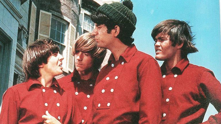 quatro homens com visual anos 60 de camisas iguais vermelhas
