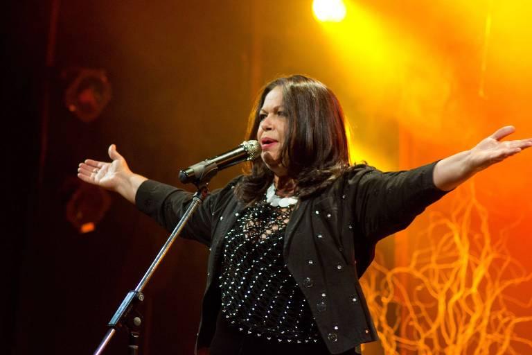 De braços abertos e roupas escuras, cantora Amelinha canta ao microfone em apresentação ao vivo