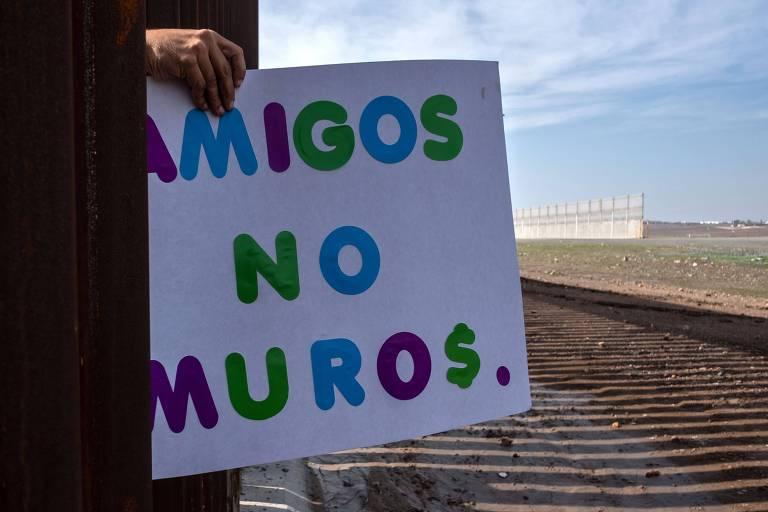 """Manifestante segura por entre a cerca na fronteira entre EUA e México um cartaz com a inscrição """"amigos, não muros"""" durante um ato nesta quinta (12) em Tijuana"""