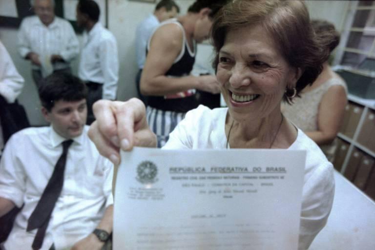 Eunice Paiva, acompanhada do filho Marcelo Rubens Paiva, recebe a certidão de óbito de Rubens Paiva (seu marido desaparecido desde 1971), entregue pela funcionária oficial de justiça, Geny Morelli, no 1º Cartório do Subdistrito da Sé