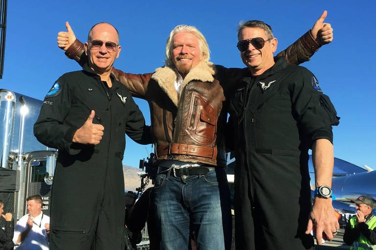 Richard Branson, no centro, comemora voo-teste com os dois pilotos que estava na nave