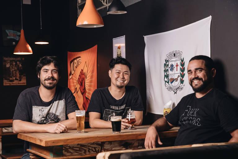 Érico Ribeiro, 31, William Okada, 33, e Lucas Cano, 32, sócios da La Fraternité Beer Shop, em Moema, zona sul de São Paulo