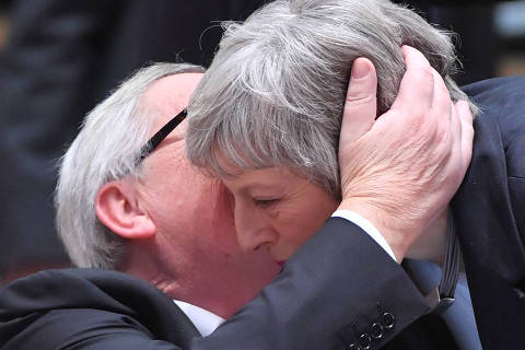 President of the European Commission Jean-Claude Juncker whispers in the ear of Britain's Prime Minister Theresa May (R) as she arrives to attend a European Summit aimed at discussing the Brexit deal, the long-term budget and the single market on December 13, 2018 in Brussels. - The 27 European leaders gather for a crucial European Union summit with the British Prime Minister seeking a compromise to save the Brexit deal. (Photo by EMMANUEL DUNAND / AFP)