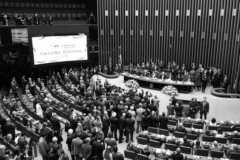 Foto do alto do plenário da camara; várias fileiras de cadeiras, à frente, uma longa mesa; parlamentares estão de pé
