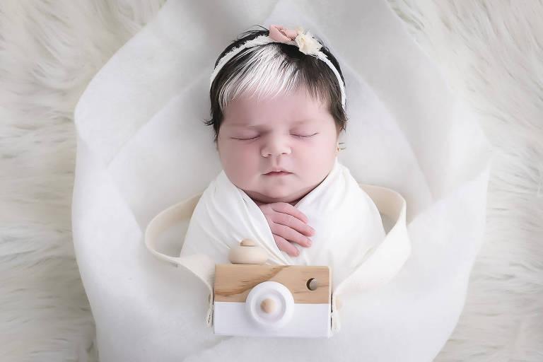 Mayah está envolta em um pano branco, dormindo. Ela tem uma franja branca e o restante do cabelo preto. Usa uma tiara de flores. Sobre ela, uma câmera fotográfica de madeira.