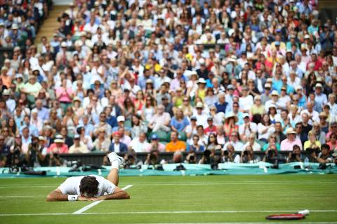 Switzerland's Roger Federer falls to the ground while trying to return to Canada's Milos Raonic during their men's semi-final match on the twelfth day of the 2016 Wimbledon Championships at The All England Lawn Tennis Club in Wimbledon, southwest London, on July 8, 2016. / AFP PHOTO / POOL / Clive BRUNSKILL / RESTRICTED TO EDITORIAL USE