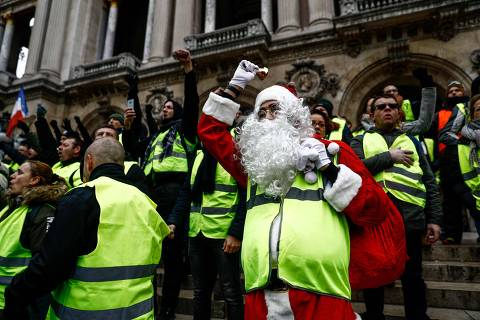 TOPSHOT - A protester dressed as Santa Claus and wearing a yellow vest (gilet jaune) demonstrates on the stairs of the Opera Garnier in Paris, on December 15, 2018 during a protest against rising costs of living they blame on high taxes in Paris, on December 15, 2018. - The