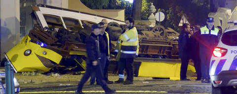 In this image taken from video, emergency service personnel work at the scene of a tram accident, Friday, Dec. 14, 2018, in Lisbon, Portugal. Portuguese emergency services say a Lisbon tram has derailed and flipped over, slightly injuring 28 people in a rush-hour accident. (Jorge Jerónimo /APTN via AP) ORG XMIT: NYDD302