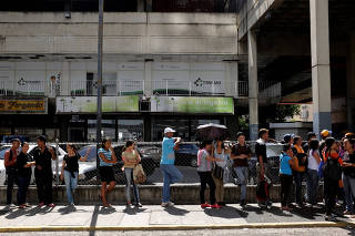People queue to buy food outside a supermarket in Caracas