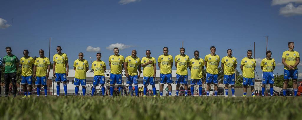Homens com calção azul e camiseta amarela perfilados em gramado