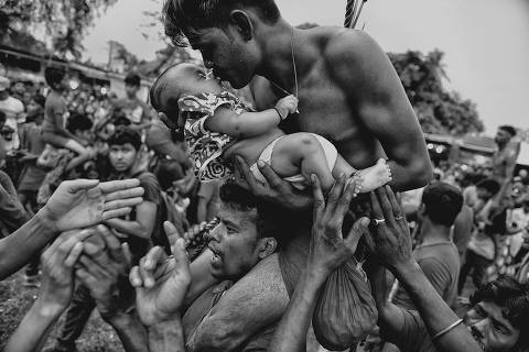 *** NATTIONAL*** Place, People: A Hindu devotee kisses his newborn baby during the Charak Puja festival in West Bengal, India. Traditional practice calls for the devotee to be pierced with a hook and sometimes swung from a rope. This painful sacrifice is done to save their children from anxiety. While covering the festival, I was able to view the religious practice from the perspective of Hindu devotees. I tried to capture the moment of love and bonding between a father and his child—and show a father's concern for his little son.Credit  Avishek Das / National Geographic Photo Contest