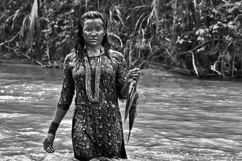 Janete, da aldeia Escondido, que usa pulseira com desenhos geométricos feitos com miçangas e segura jijus pescados no rio