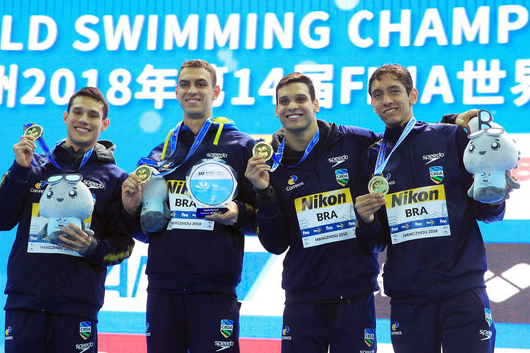 Quatro homens de preto seguram medalhas de ouro e sorriem