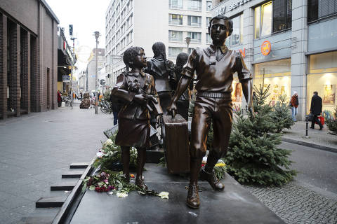 People pass a commemorative memorial statue to perpetuating the memory of the 'Kindertransport' (children transport) near Friedrichstrasse train station in central in Berlin, Germany, Monday, Dec. 17, 2018. Germany has agreed to one-time payments for survivors, primarily Jews, who were evacuated from Nazi Germany as children, many of whom never saw their parents again. (AP Photo/Markus Schreiber) ORG XMIT: BER103