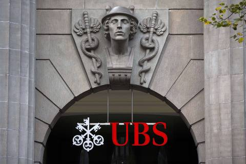 (FILES) - A picture taken on October 13, 2012 in Zurich shows the logo of Swiss banking giant UBS at the entrance to one of their branches. French investigators have placed Swiss bank UBS under formal investigation on suspicion that it tried to persuade rich French clients to open undeclared accounts in Switzerland, a legal source said.           AFP PHOTO / FABRICE COFFRINI ORG XMIT: FAB027