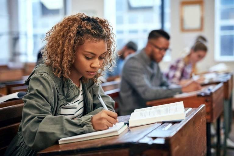Dentro de sala de aula, aluna escreve em seu caderno