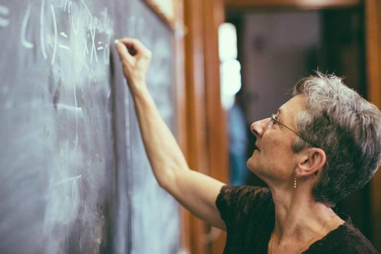 Professora escreve em quadro negro