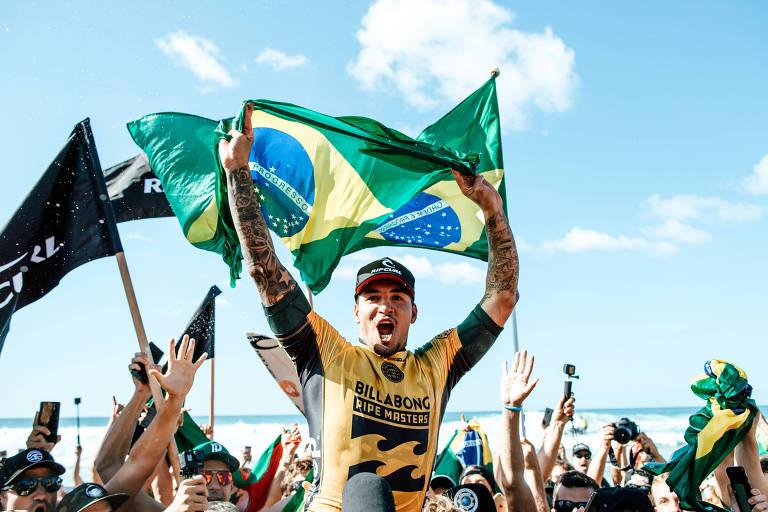 Gabriel Medina comemora o título no Havaí segurando uma bandeira do Brasil