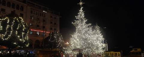 This picture taken on December 18, 2018, shows a man passing by Christmas tree in Thessaloniki on December 18, 2018. (Photo by Sakis MITROLIDIS / AFP)