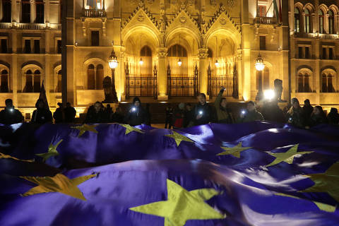 People hold a big European Union flag during a protest against a proposed new labor law, billed as the