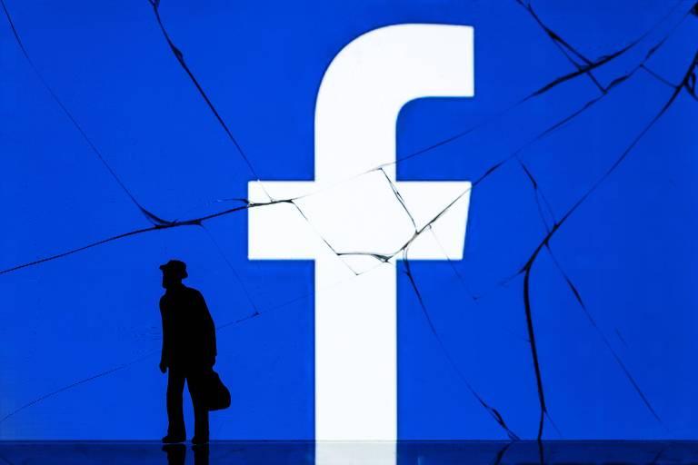 Homem em frente à logomarca do Facebook exibida em telão em Paris