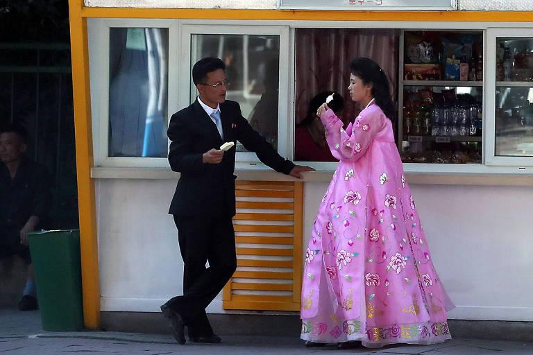 Com vestido tradicional, norte-coreana toma sorvete em quiosque de rua em Pyongyang