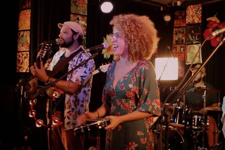 Os cantores Rodrigo Régis (de boina, camisa florida e violão) e Tata Alves (de vestido florido, pandeiro na mão e cabelos encaracolados pintados de loiro) se apresentam em show