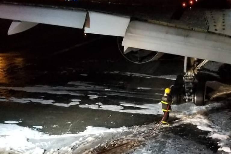 Bombeiros fazem rescaldo de fuselagem de avião que fez pouso de emergência no aeroporto de Confins, em Minas