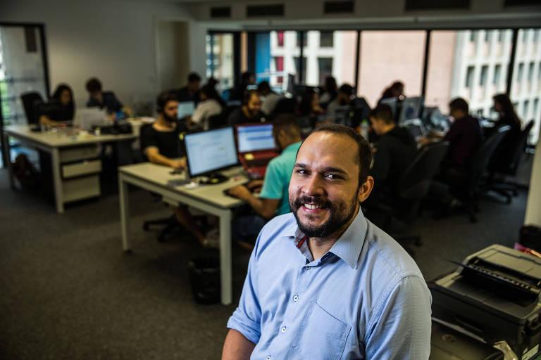 Homem em primeiro plano, com camisa azul, sorri para câmera. Atrás dele há uma sala de trabalho com computadores e pessoas trabalhando