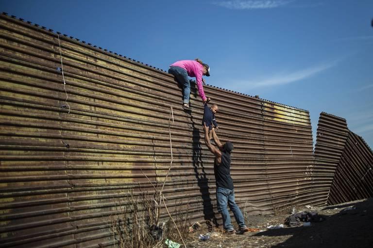 Migrantes passam criança por cima de grade