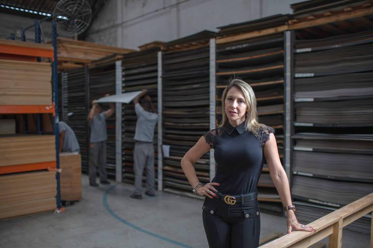Mulher loira de preto, em pé, em primeiro plano, olha para a câmera enquanto três homens trabalham em pilha de madeira ao fundo