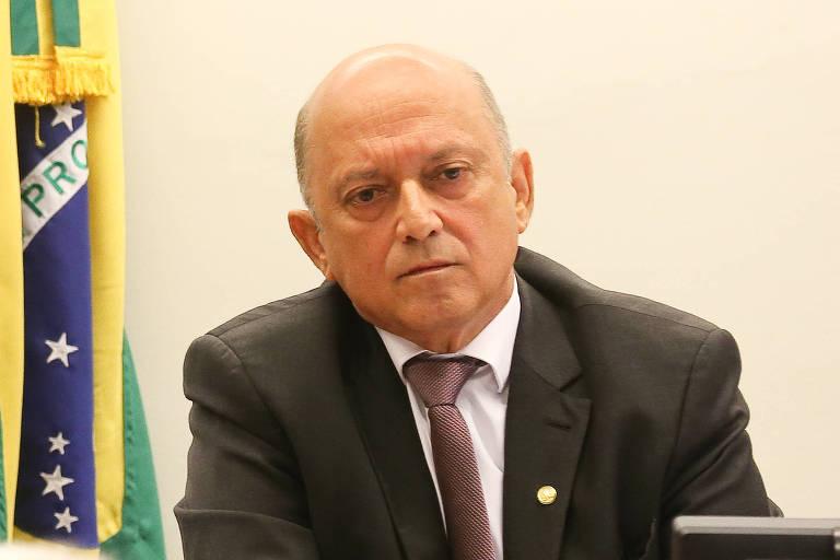 De terno e com a bandeira do Brasil no fundo, Lelo Coimbra olha pra câmera
