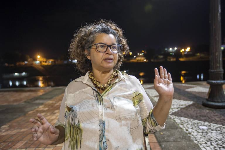 Angela Mendes, filha de Chico Mendes, em meio a uma rua, levanta uma das mãos