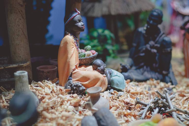 Em cenário que remete ao de uma tribo africana, a mulher segura uma cesta de frutas enquanto o bebê repousa em seu colo. À distância, o homem observa a cena. Nele, a maior parte das figuras é de resina.