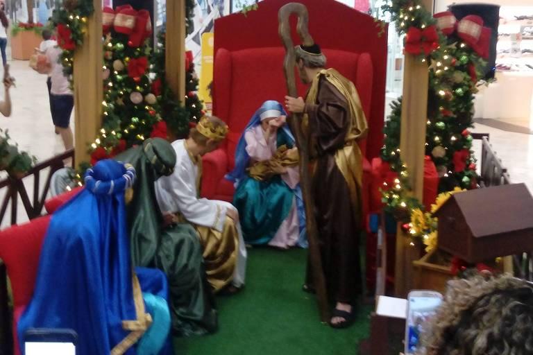 """Encenação de """"A Visita dos Reis Magos"""" no shopping Interlagos, em São Paulo. Os Reis estão sentados me fila, um de azul, um de verde, um de branco. Maria segura bebê e José está em pé com um cajado"""