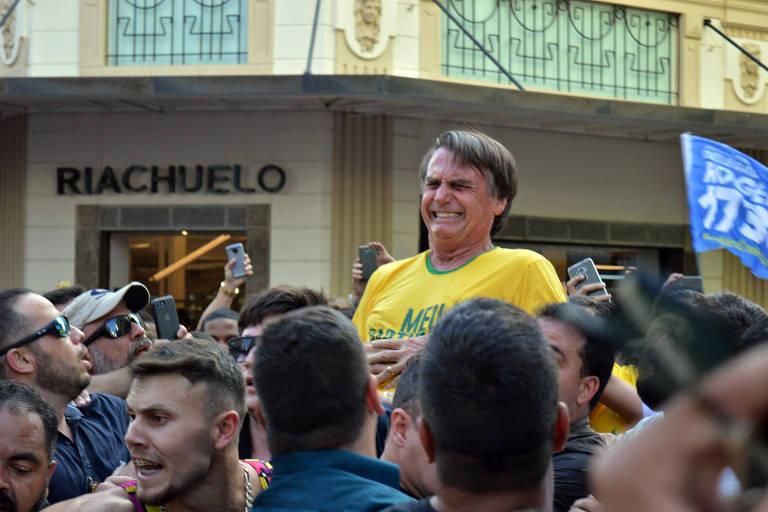 Bolsonaro está de camiseta verde e amarela, com expressão de dor. Ele está levantado em meio à multidão
