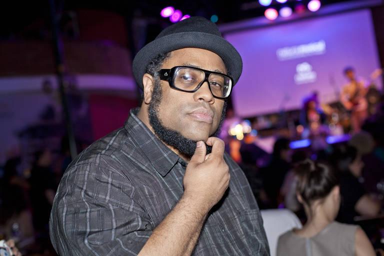 De chapéu, camisa e óculos pretos, cantor BNegão passa a mão na barba enquanto é fotografado