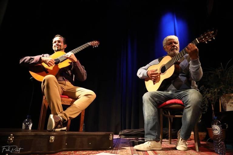 Violonistas Dinho Nogueira (à esquerda) e Zé Barbeiro (à direita) se apresentam sentados, com seus violões, em show
