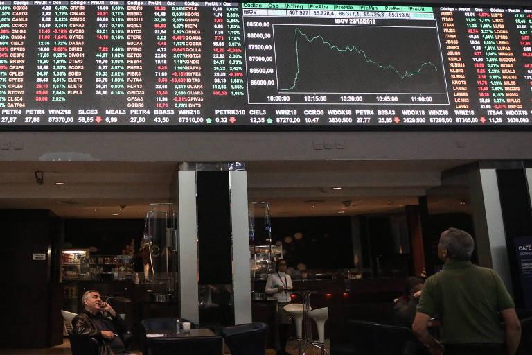 Na foto, pessoas estão de costas para a câmera, olhando para um painel eletrônico da Bolsa de Valores, onde as cotações de diversas ações podem ser vistas em verde (quando estou subindo) e em baixa (quando estão em queda).