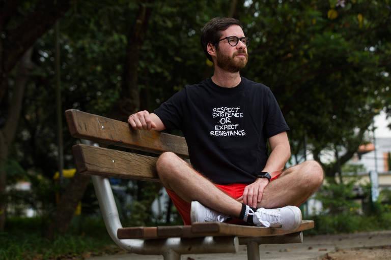 O jovem Caio Aissa sentado de pernas cruzadas em um banco de praça