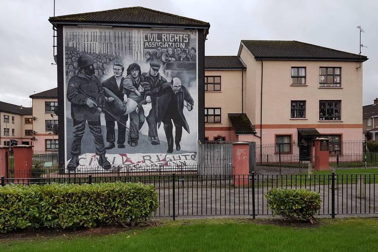 Pintura mural em enclave nacionalista (pró-reunificação com a República da Irlanda) de Derry, no oeste da Irlanda do Norte, representa cena do Domingo Sangrento, em janeiro de 1972, quando soldados do Exército britânico mataram 14 participantes de uma marcha pelos direitos civis realizada no local